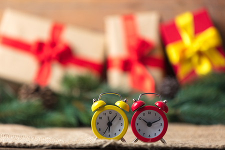 old desk: Alarm clock on jute and Christmas gifts on background