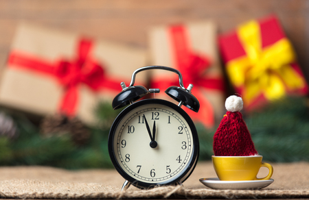 old desk: Christmas gifts and cup of tea with alarm clock on wooden and jute background Stock Photo