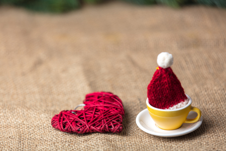 Christmas tea with Santa Claus hat and heart shape toy on jute background