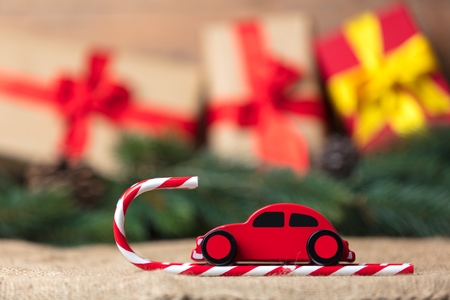 desk: Red toy car and lollipop with hat on Christmas gifts background