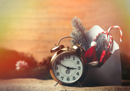 Christmas gifts in envelope near alarm clock on wooden background