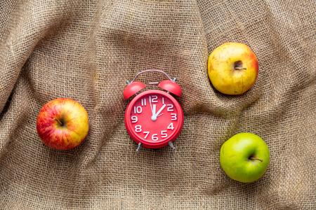 Apples and alarm clock on jute sack background. Autumn season harvest Stock Photo