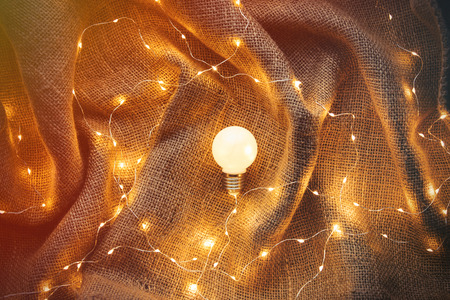 Bulb lamp and Fairy Lights around on jute background