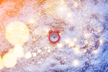 Vintage alarm clock and Fairy Lights on snow background. Concept for Christmas or Valentines Day Holidays Stock Photo
