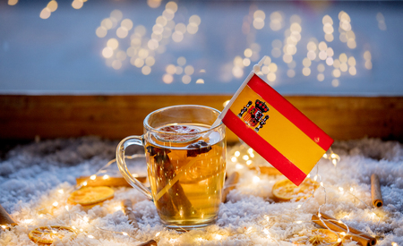 Cup of tea and flag of Spain on snow and fairy lights background. Christmas time decoration