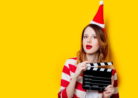 Portrait of young redhead woman in Santa Claus hat and striped shirt with filmmaking clapperboard on yellow background. Christmas time Foto de archivo