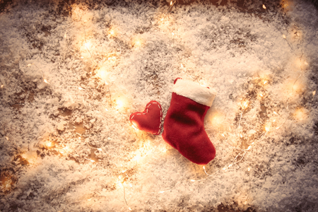 Heart shape toy and Fairy Lights with Santa Claus sock on snow background. Concept for Christmas or Valentines Day Holidays