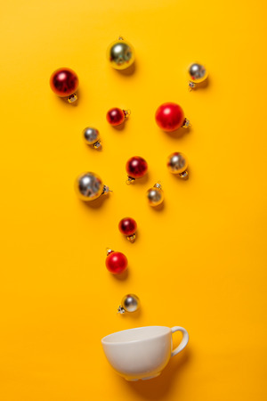 White cup and Christmas baubles on yellow background Stock Photo