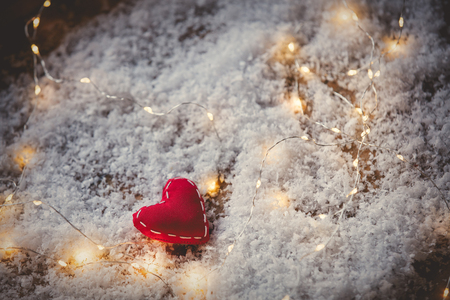 Heart shape toy and Fairy Lights on snow background. Concept for Christmas or Valentines Day Holidays  Imagens
