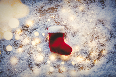 Santa Claus sock and Fairy Lights on snow background. Concept for Christmas or Valentines Day Holidays