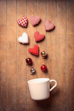 White cup on lying on side with heart shapes on wooden background. Hight angle of view of Christmas concept