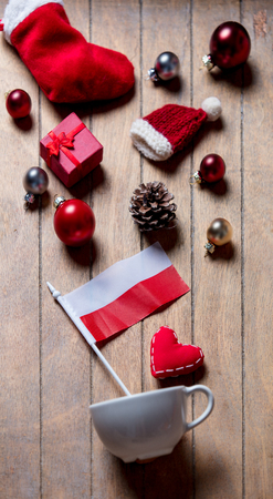 White cup and Poland flag with Christmas decoration on wooden background Stock Photo