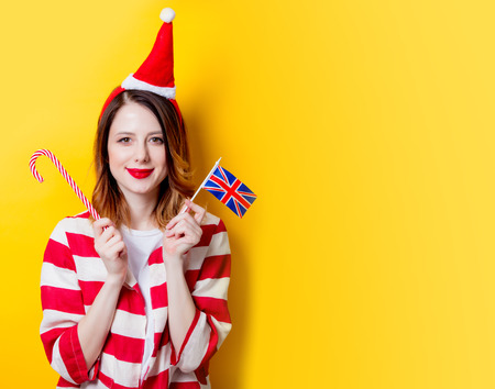 Portrait of young redhead woman in Santa Claus hat and striped shirt with Great Britain flag and candy cane on yellow background. Christmas time Stock Photo
