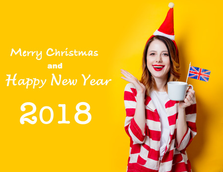 Portrait of young redhead woman in Santa Claus hat and striped shirt with Great Britain flag and cup of tea on yellow background. Christmas time