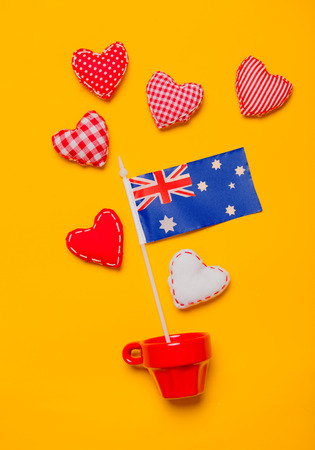 Red cup with heart shapes and flag of Australia on yellow background. Stock Photo