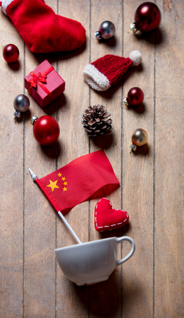 White cup and China flag with Christmas decoration on wooden background Stock Photo