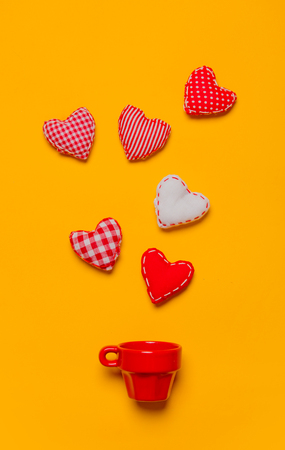 Valentines Day heart shapes and red cup on yellow background