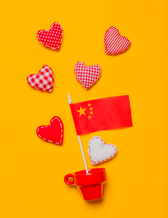 Red cup with heart shapes and flag of China on yellow background.