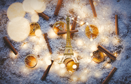 Eiffel tower toy and lemons with cinnamons on snow and fairy lights background