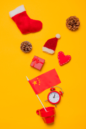 Red cup and China flag with Christmas presents on yellow background. Above view Stock Photo