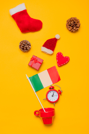 Red cup and Italy flag with Christmas presents on yellow background. Above view