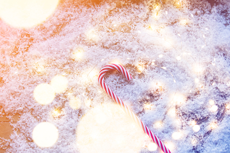 Candy cone on snow with Fairy lights around. Christmas time