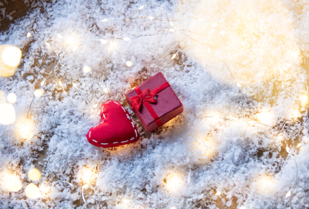 Heart shape toy and Fairy Lights with gift box on snow background. Concept for Christmas or Valentines Day Holidays