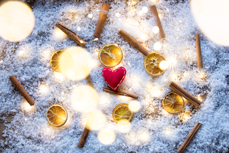 Hearth shape and cinnamon with lemon on snow background