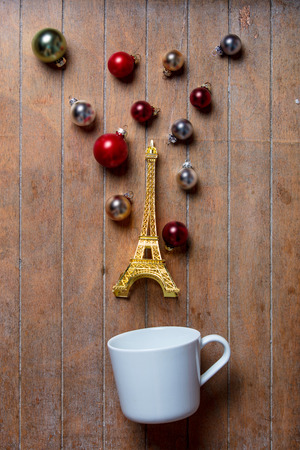 White cup on lying on side with Eiffel tower toy and Christmas baubles on wooden background. Hight angle of view