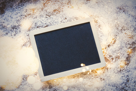 Blackboard on snow and fairy lights around