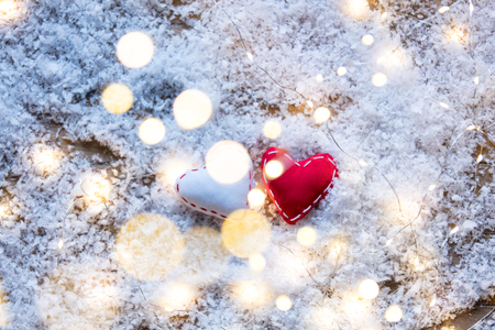Two Heart shape toys and Fairy Lights on snow background. Concept for Christmas or Valentines Day Holidays