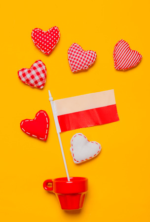 Red cup with heart shapes and flag of Poland on yellow background.