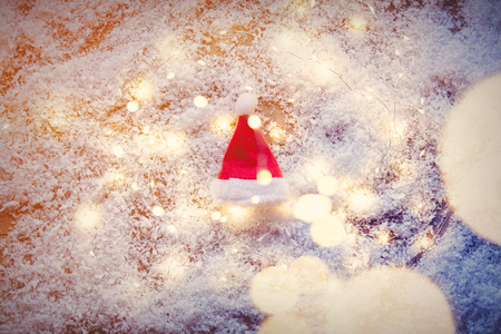 Santa Claus hat and Fairy Lights on snow background. Concept for Christmas or Valentines Day Holidays