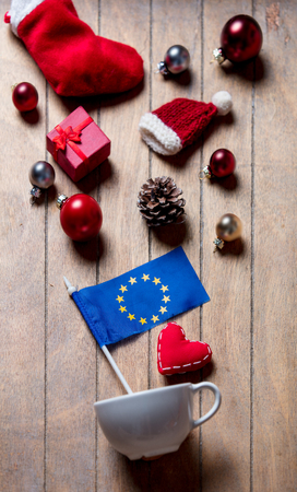 White cup and europe Union flag with Christmas decoration on wooden background