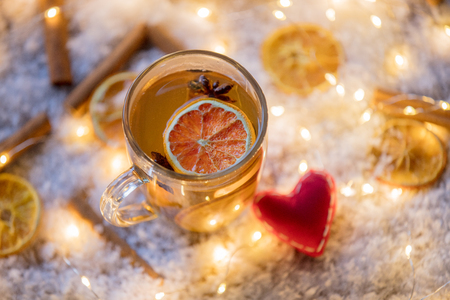 Heart shape and cup of tea with lemon on snow and fairy lights background Imagens