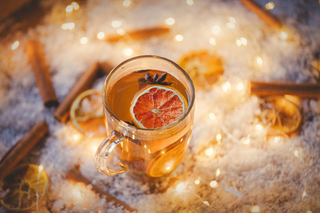 Glass cup with tea and lemons with cinnamons on snow and fairy lights background. Christmas time  Imagens