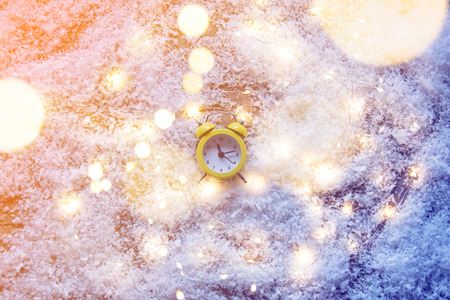 Vintage alarm clock and Fairy Lights on snow background. Concept for Christmas or Valentines Day Holidays Imagens