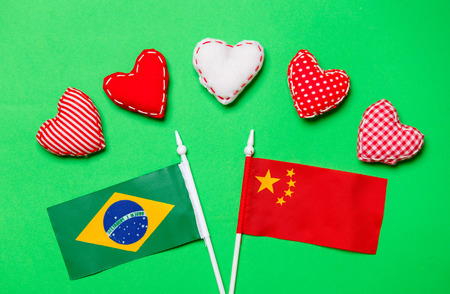 Valentines Day heart shapes and flags of Brasil and China on green background