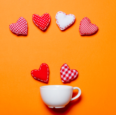 White cup and heart shapes on orange background