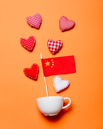 White cup and heart shapes with China flag on orange background Stock Photo