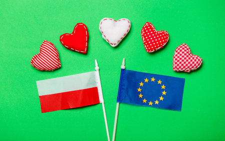 Valentines Day heart shapes and flag of Europe Union and Poland on green background