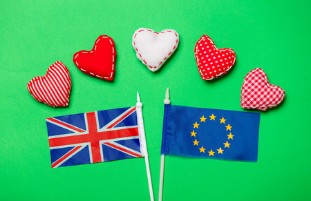 Valentines Day heart shapes and flag of Europe Union and United Kingdom on green background