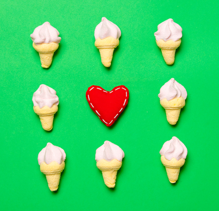 Heart shape and marshmallows on green background