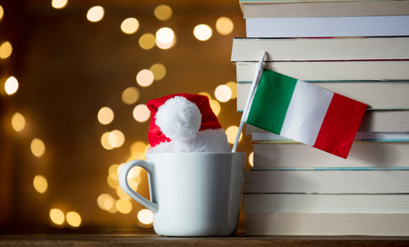 White cup and Christmas hat with Italy flag near books on fairy lights background
