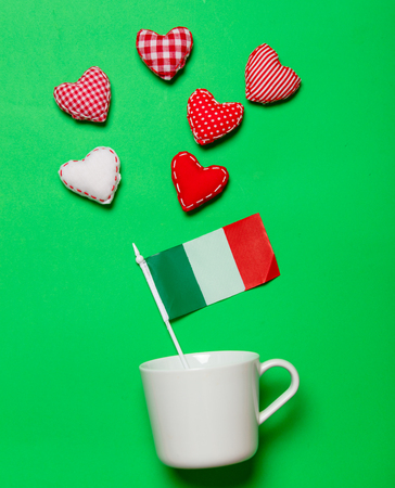 White cup and flag of Italy with heart shapes on green background