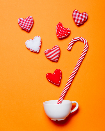 White cup and candy cane with heart shapes on orange background Stock Photo