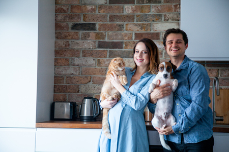 Young family, pregnant woman and her partner or husband with dog and cat at kitchen Stockfoto