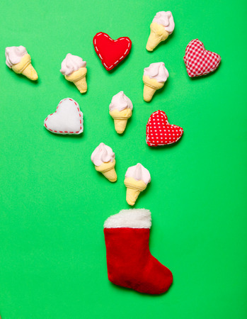 Red Christmas sock and marshmallows with heart shapes on green background