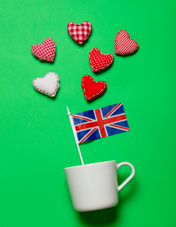 White cup and flag of United Kingdom with heart shapes on green background