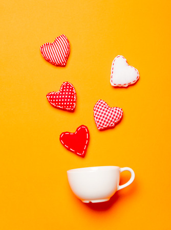 Heart shapes and white cup on yellow background Stock Photo